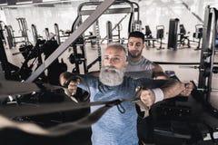 成熟运动员有与教练员的锻炼在运动中心 免版税图库摄影