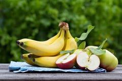 成熟香蕉和苹果在木桌上 免版税库存照片