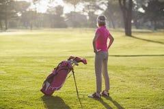 成熟高尔夫球运动员背面图用在臀部的手 免版税图库摄影