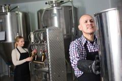 成熟高兴的男性啤酒厂工作者画象  库存图片