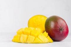 成熟黄色芒果整个与红色和绿色边和稀烂被切的半特写镜头在软的白木委员会 免版税库存图片
