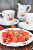 成熟,开胃草莓在白色板材驱散了 免版税库存图片
