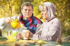 成熟从一个茶壶的人倾吐的茶到他的妻子 库存照片