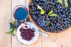 成熟黑堂梨属灌木Aronia melanocarpa新鲜的汁液和果酱在玻璃和莓果的在木背景的罐 库存图片