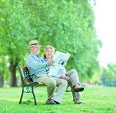 成熟读新闻的男人和妇女户外 库存照片