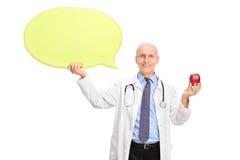 成熟医生拿着苹果的和讲话起泡 免版税库存照片