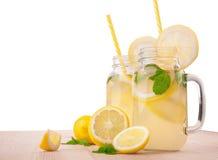 成熟黄色柠檬、新鲜薄荷和矿泉水在两个透明水罐在一张轻的木桌上,隔绝在白色背景 免版税库存照片