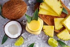 成熟黄色菠萝、椰子、圆滑的人与切片石灰和冰 概念健康食物 库存图片