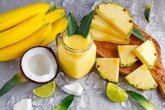 成熟黄色菠萝、椰子、圆滑的人与切片石灰和冰 概念健康食物 图库摄影