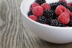 成熟黑莓和莓在白色碗在老橡木桌上 免版税库存照片