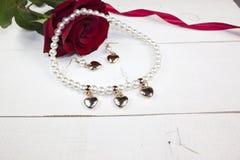 成珠状与耳环的项链有在白色木头的金黄心脏的 免版税库存照片