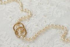 成珠状与金黄圆环的项链在白色鞋带 免版税库存照片