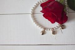 成珠状与金黄心脏的项链在白色木头 免版税库存照片