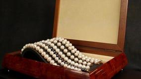 成珠状在棕色木小箱,首饰的镯子由珍珠,在垫座装饰的珍珠镯子制成的迷人 股票视频