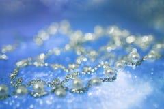 成珠状在模糊的蔚蓝色背景的银色项链 免版税图库摄影