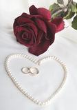 成珠状心脏、玫瑰和婚戒 库存照片