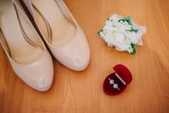成珠状有一朵钮扣眼上插的花和一个箱子的新娘鞋子有圆环的 库存照片