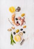 组成用橄榄和柠檬的海鲜在白色木桌上 库存图片
