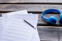 组成的音乐与蓝色耳机和在木书桌上 免版税库存图片