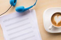 组成的音乐注意顶视图用咖啡和蓝色耳机 图库摄影
