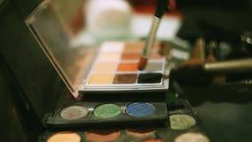 组成设计师投入刷子在五颜六色的明亮的眼影 化妆用品 beauvoir 妇女 镜子 股票视频