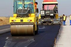 成水平在跑道的压路机新鲜的沥青路面作为多瑙河三角洲国际机场拓展计划一部分 免版税库存图片