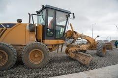 成水平在建造场所的平地机石渣 免版税库存照片