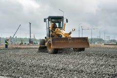成水平在建造场所的平地机石渣 免版税库存图片