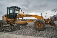 成水平在建造场所的平地机石渣 库存照片