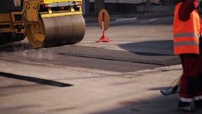 成水平沥青的修路工作者使用犁耙,当在通过后面的压路机时 股票视频