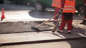 成水平沥青的修路工作者使用犁耙,当在通过后面的压路机时 股票录像