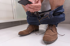成年男性佩带的牛仔裤和鞋子使用电话,当坐时 免版税库存照片