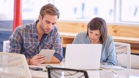 成年男性和女性商务伙伴繁忙工作在办公室 免版税库存图片