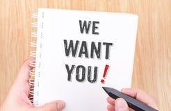 我们想要您!在白色圆环包扎工具笔记本的词有手holdi的 库存图片