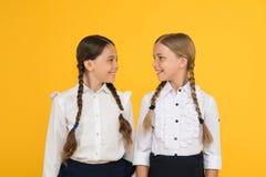 我们爱研究 制服的愉快的孩子 黄色背景的女孩 友谊和妇女团体 r 库存照片