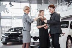 我们的第一辆汽车 微笑美丽的愉快的妇女显示钥匙对他们买与愉快她的丈夫的一辆新的汽车 库存图片