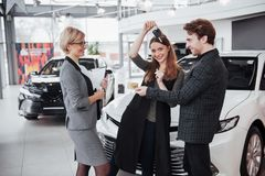 我们的第一辆汽车 微笑美丽的愉快的妇女显示钥匙对他们买与愉快她的丈夫的一辆新的汽车 免版税库存图片