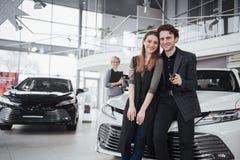 我们的第一辆汽车 微笑美丽的愉快的妇女显示钥匙对他们买与愉快她的丈夫的一辆新的汽车 库存照片