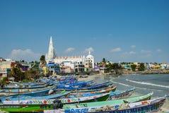 我们的赎金在五颜六色的房子后的寺庙教会的夫人渔船占领的沙滩的在科摩林角在印度 免版税库存照片