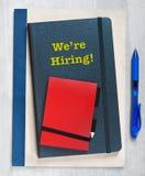 我们聘用!在堆写的文本笔记本,在木背景的一支蓝色笔旁边 库存照片