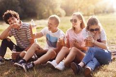 我们获得乐趣!快乐的高兴的朋友有喜悦并且度过室外的夏日,微笑得快乐,饮料冷的萍果汁或柠檬水,女孩佩带 库存图片