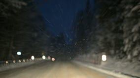 我们通过沿雪道的一个冬天森林驾驶在晚上 在飞行在挡风玻璃的雪剥落的焦点 股票视频