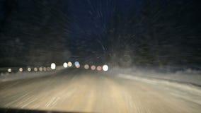 我们通过沿雪道的一个冬天森林驾驶在晚上 在飞行在挡风玻璃的雪剥落的焦点 股票录像