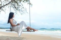 我其他看到暑假工作 放松和享受在沙子海滩的生活方式妇女摇摆,塑造有白色礼服的惊人的妇女在tr 免版税图库摄影