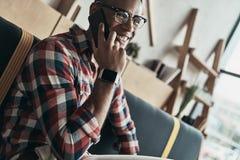 我可以完全使它工作!英俊的年轻人谈话在他的sm 免版税库存照片