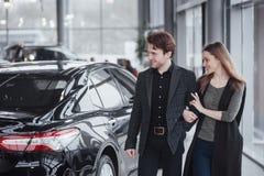 我喜欢这辆汽车 站立在经销权的美好的年轻夫妇选择汽车买 免版税库存照片
