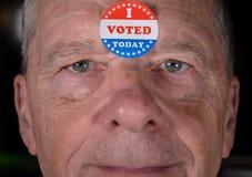 我投票了纸贴纸今天供以人员有温暖的微笑的前额在照相机 图库摄影