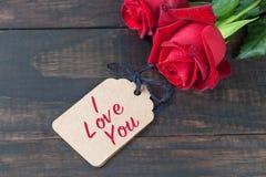 我爱你与玫瑰的文本在黑暗的木头 库存照片