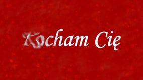 我爱你在波兰Kocham Cie的文本转向从左边的尘土在红色背景 免版税库存照片