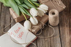 我爱你在笔记本的词组有在桌上的花的 免版税库存图片